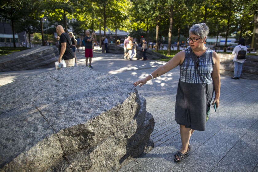 A visitor touches one of the granite slabs that recognize an initially unseen toll of the 9/11 terrorist attacks: firefighters, police and others who died or fell ill after exposure to toxic materials unleashed in the wreckage.