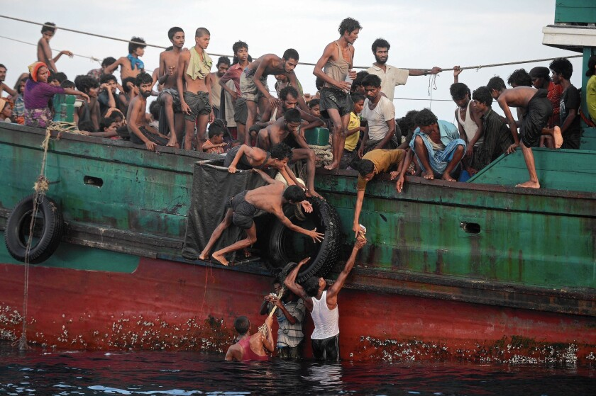 Rohingya migrants pass food supplies dropped by a Thai army helicopter to others aboard a boat drifting in Thai waters off the southern island of Koh Lipe on May 14.