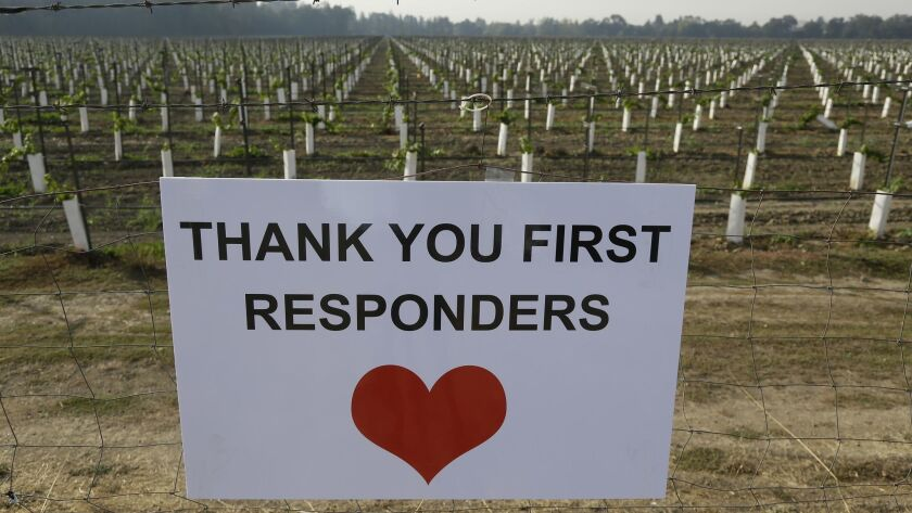 A sign thanking first responders hangs by a newly planted vineyard in Napa. With the winds dying down, fire crews gained ground as they battled wildfires that have devastated California wine country.