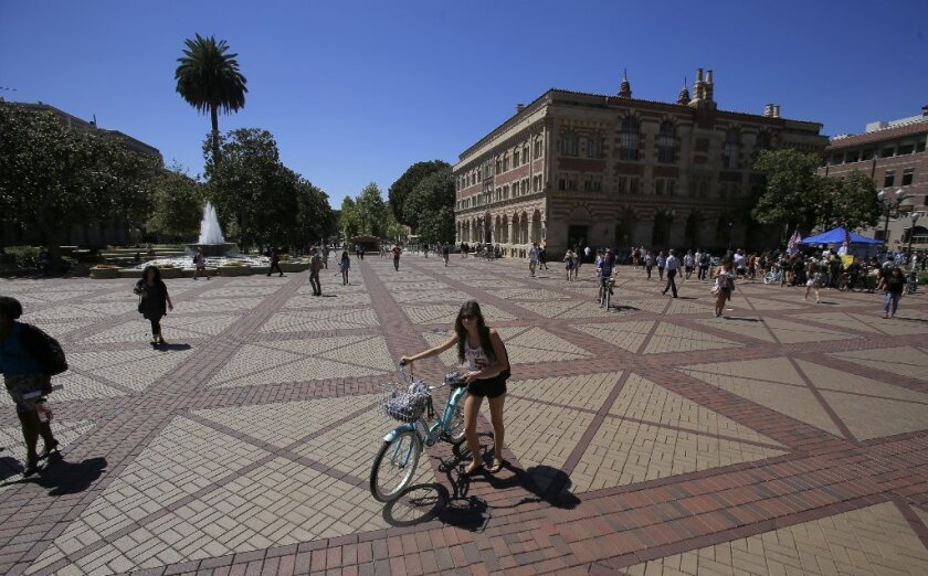 A student walks her bike through center campus at USC in September. With a freshman acceptance rate of less than 18%, USC ranks 25th among national universities, according to U.S. News & World Report.