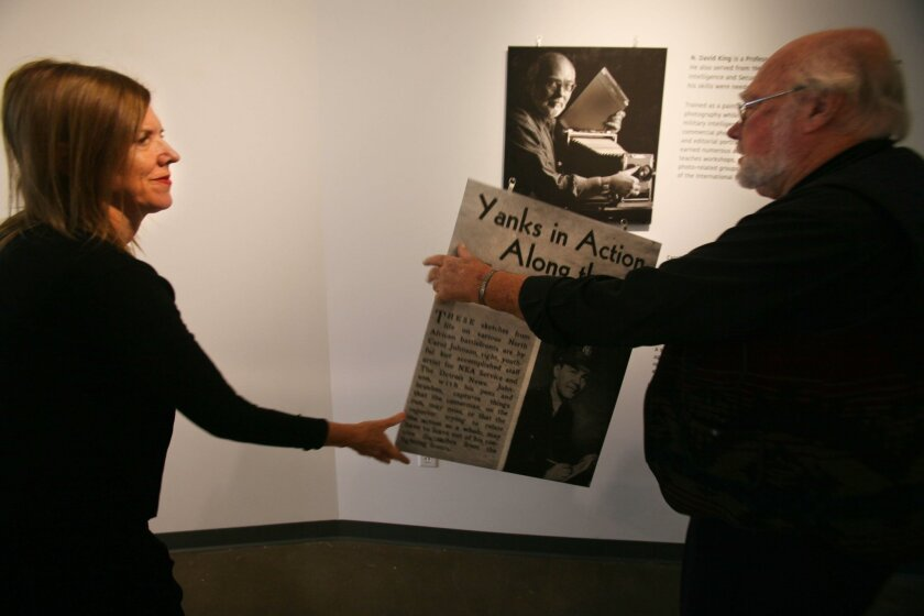 Candice Lopez, left, hands a display panel to photographer David King as they finish hanging an exhibit at San Diego City College's Luxe Gallery on Friday.