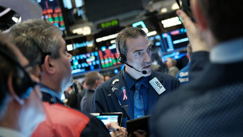 Traders work on the floor of the New York Stock Exchange in New York City on April 8. Markets are reacting as President Trump considers placing Herman Cain, a former pizza executive and presidential candidate, to a seat on the Federal Reserve Board.