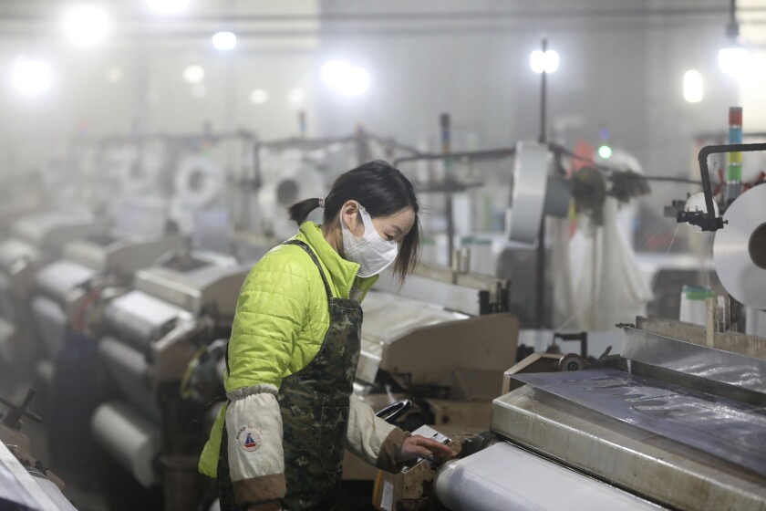 In this Feb. 27, 2020 photo, a woman works on a spinning mill in a textile factory in Hangzhou in eastern China's Zhejiang Province. A gauge of Chinese manufacturing plunged in February by an even wider margin than expected after efforts to contain a virus outbreak shut down much of the world's second-largest economy. (Chinatopix via AP)