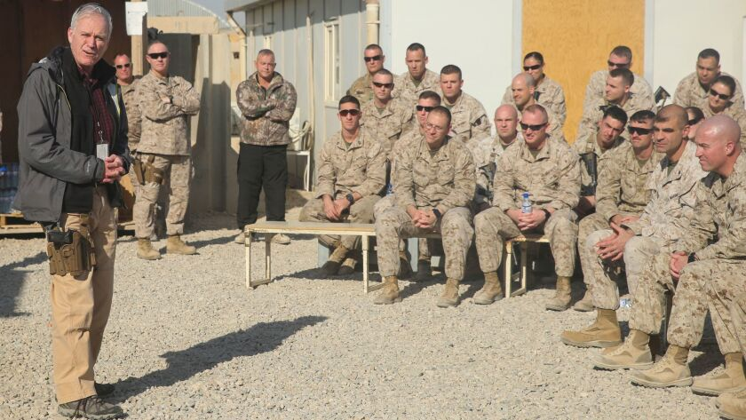 Secretary of the Navy Richard V. Spencer speaks with Marines and Sailors assigned to Task Force Southwest at Camp Shorab, Afghanistan, on Dec. 23. A Beretta 9mm pistol appears to be holstered at his side.