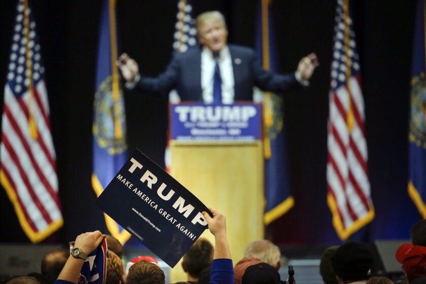 A supporter holds up a sign as Republican presidential candidate, businessman Donald Trump addresses the crowd during a campaign rally Monday, Feb. 8, 2016, in Manchester, N.H. (AP Photo/David Goldman)