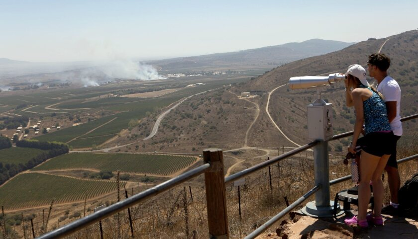 Israeli tourists watch smoke rising near the Syrian-Israeli border Wednesday amid fighting between the Syrian army and rebels over the control of the Quneitra border crossing.