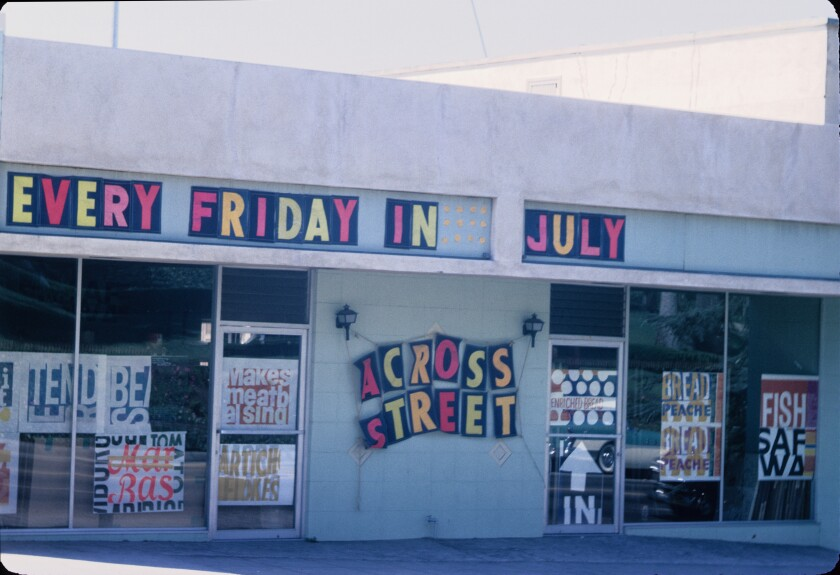 """A vintage color photo shows the studio's windows covered in bright prints bearing phrases such as """"makes meatball sing"""""""