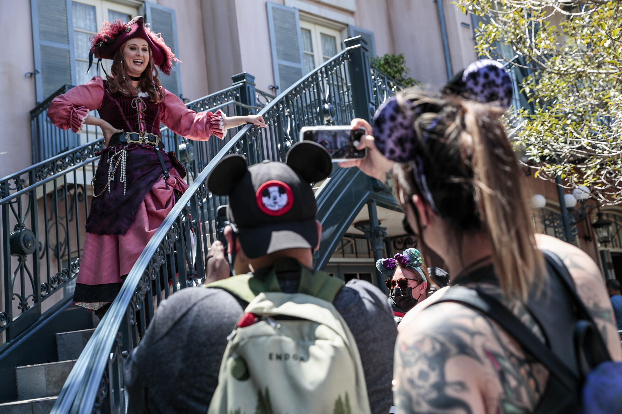 A woman in a pirate costume chats with people wearing mouse ears