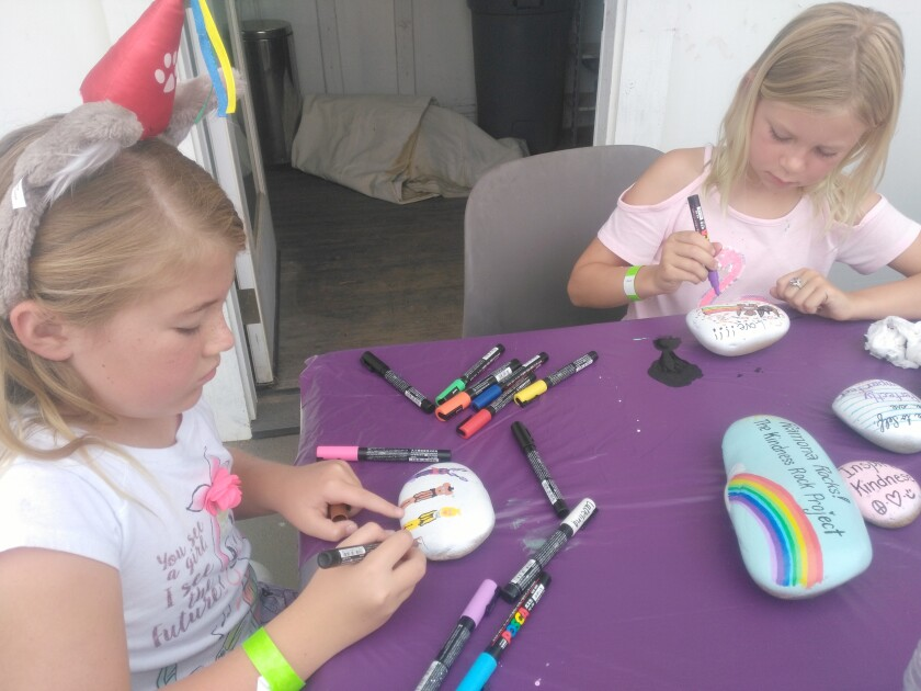 """Evie Schenk, left, and Kayleigh Maginnis paint their """"Kindness Rocks"""" that can be placed around the world for others to find."""