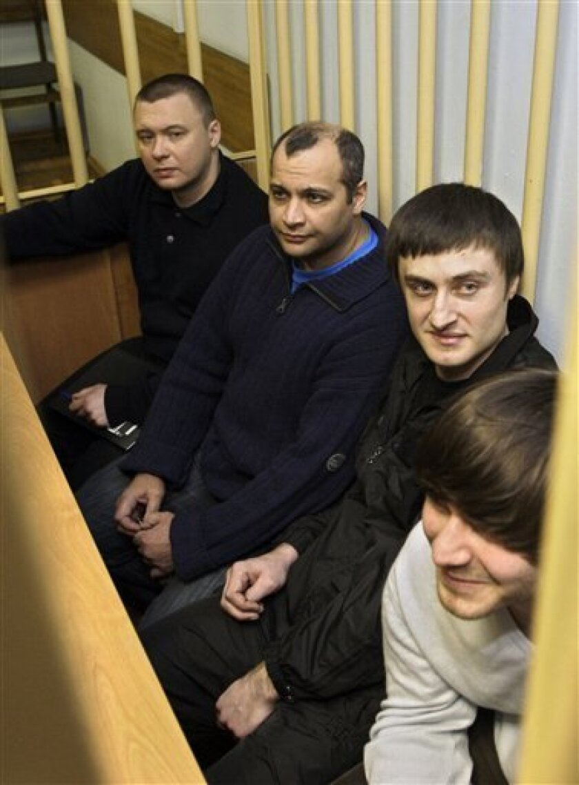 From left: Pavel Ryguzov, Sergei Khadzhikurbanov, Ibragim and Dhzabrail Makhmudov sit behind bars at a court room in Moscow in this Nov. 17, 2008 file picture. The suspects being tried on murder charges are Sergei Khadzhikurbanov _ a former Moscow police officer _ and the Makhmudov brothers, Ibragim and Dzhabrail. A lawyer says a Moscow court has reversed itself and ordered the murder trial of journalist Anna Politkovskaya closed to the public. Lawyer Karinna Moskalenko says the Moscow District Military Court made the decision after jurors refused to enter the courtroom fearing publicity from journalists covering the trial. (AP Photo/Sergey Ponomarev, file)