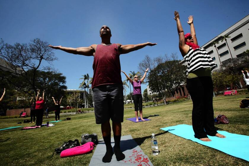 Jovon Washington, left, and Nay Jospine, both of Echo Park, participate in a free yoga class on the lawn of Grand Park.