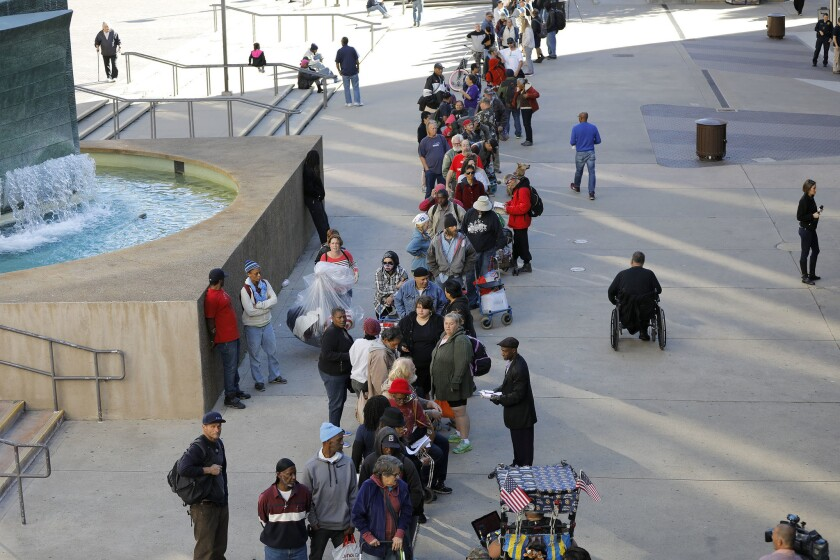 People attending Project Homeless Connect at Golden Hall wait in line for the doors to open.
