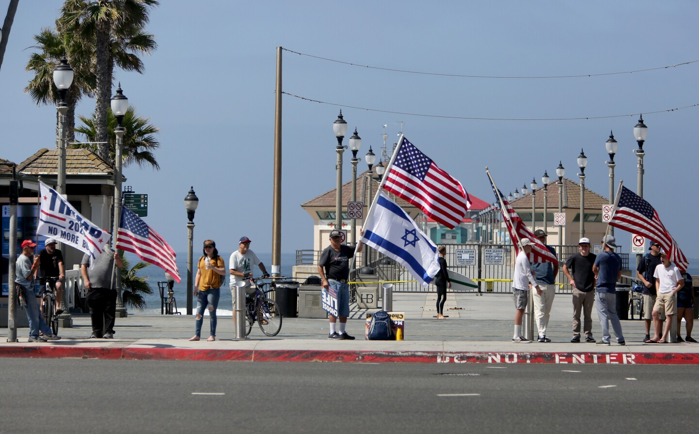 Some protesters hold flags and signs up at the entrance to the pier in Huntington Beach on Saturday.