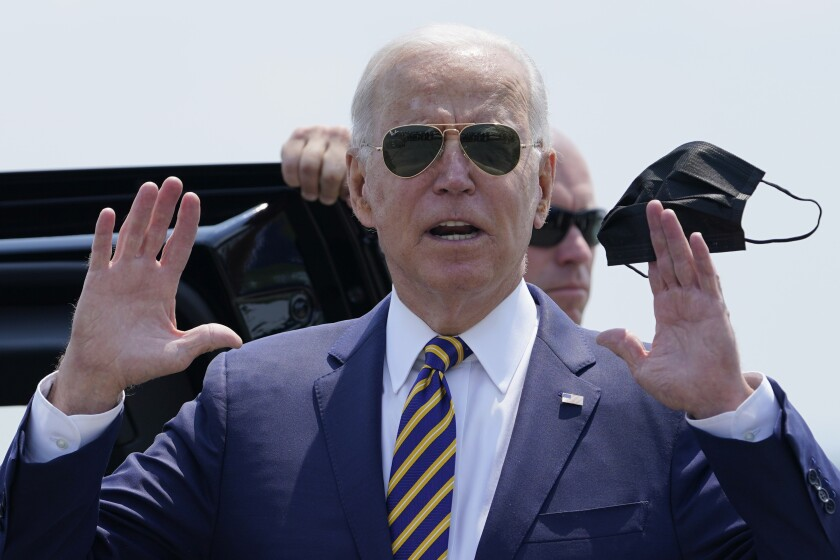 Joe Biden, in suit and aviator sunglasses, holds a mask.