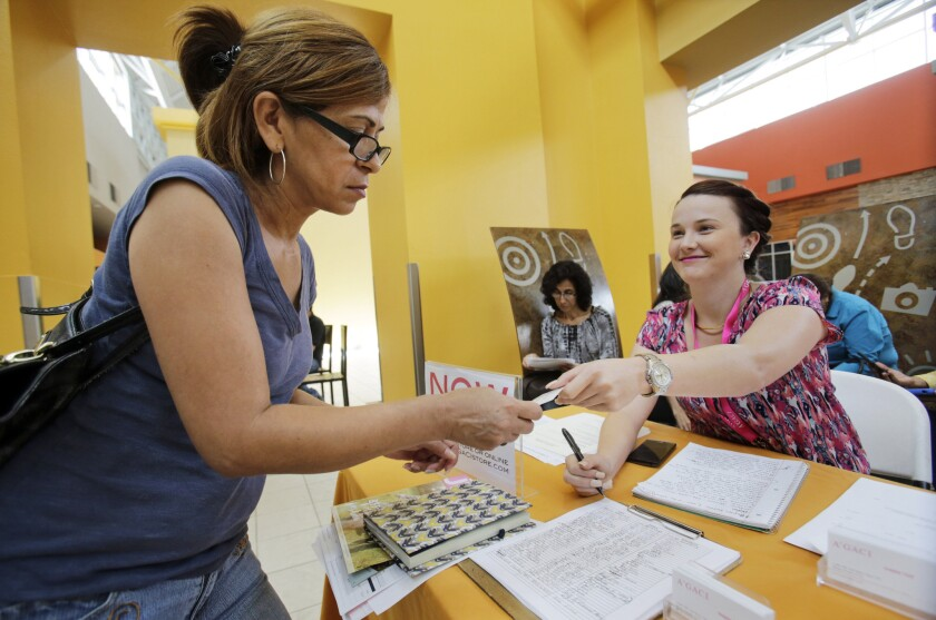 A'GACI clothing store manager Marcie Lowe, right, gives her card to job applicant Xionara Garcia at a job fair in Miami on Oct. 6, 2015.