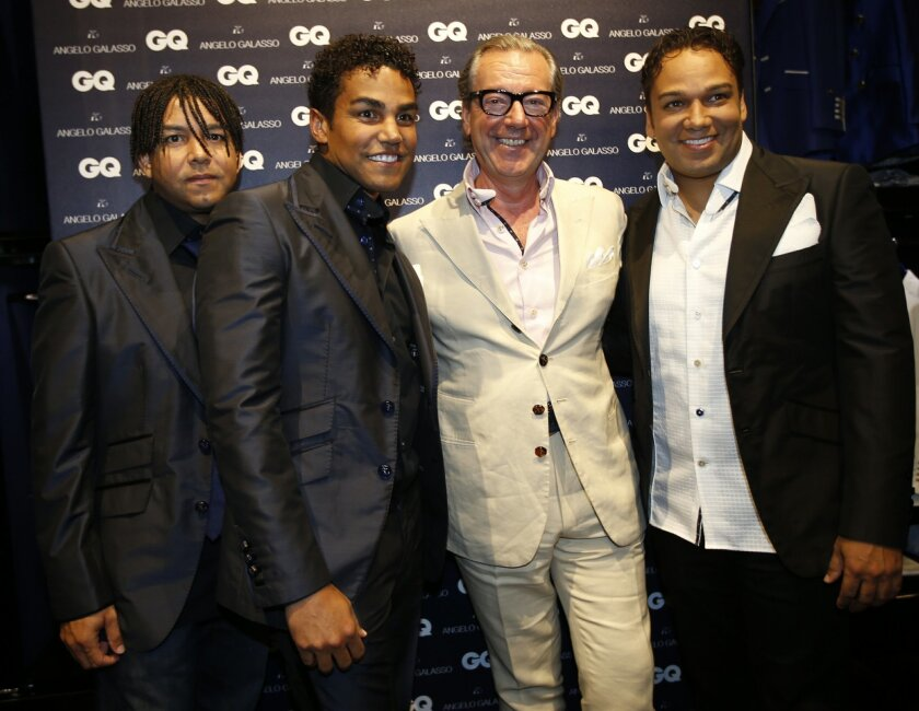 3T pop group members from left, Taj, TJ and Taryll, nephews of late pop star Michael Jackson pose with Italian fashion designer Angelo Galasso, second right, as they attend a presentation of Angelo Galasso men's Spring-Summer 2015 collection, part of the Milan Fashion Week, unveiled in Milan, Italy, Monday, June 23, 2014. (AP Photo/Luca Bruno)