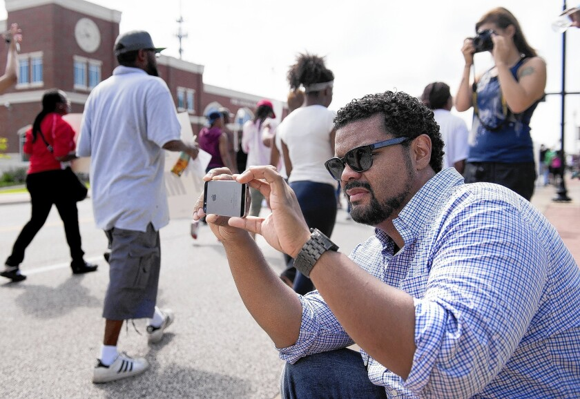 St. Louis Alderman Antonio French photographs protesters marching through downtown Ferguson, Mo.