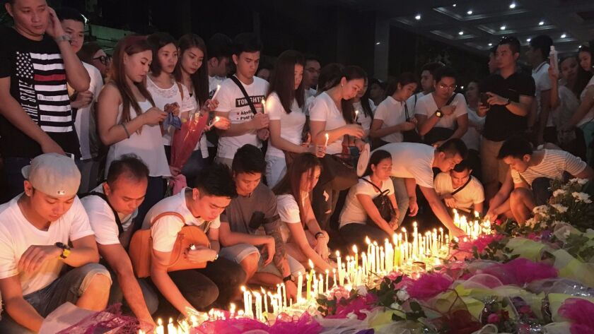 Mourners in the Philippine capital, Manila, light candles and lay flowers in front of a memorial out