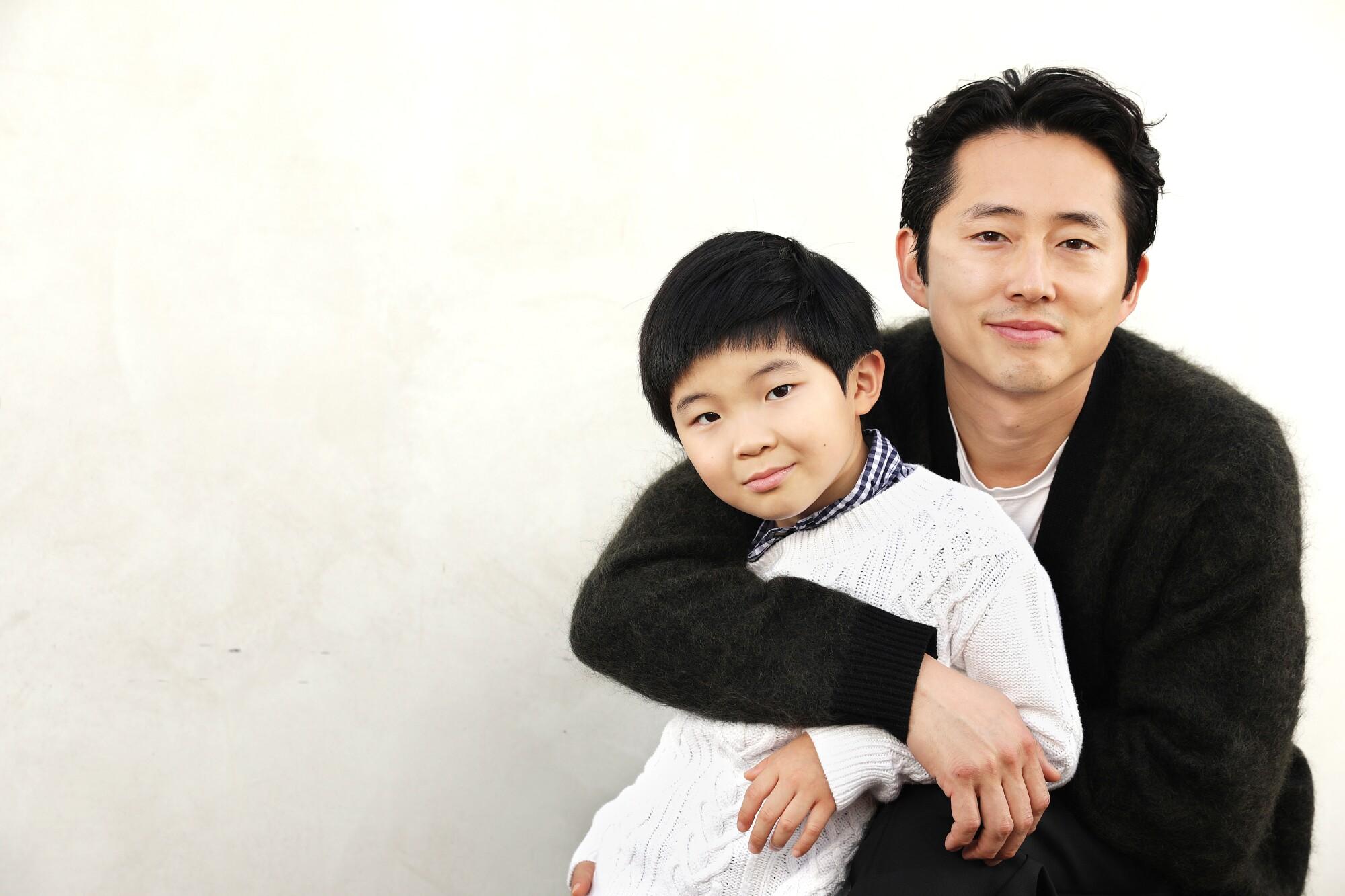 """Actor Steven Yeun embraces Alan Kim, who plays his son in """"Minari."""""""