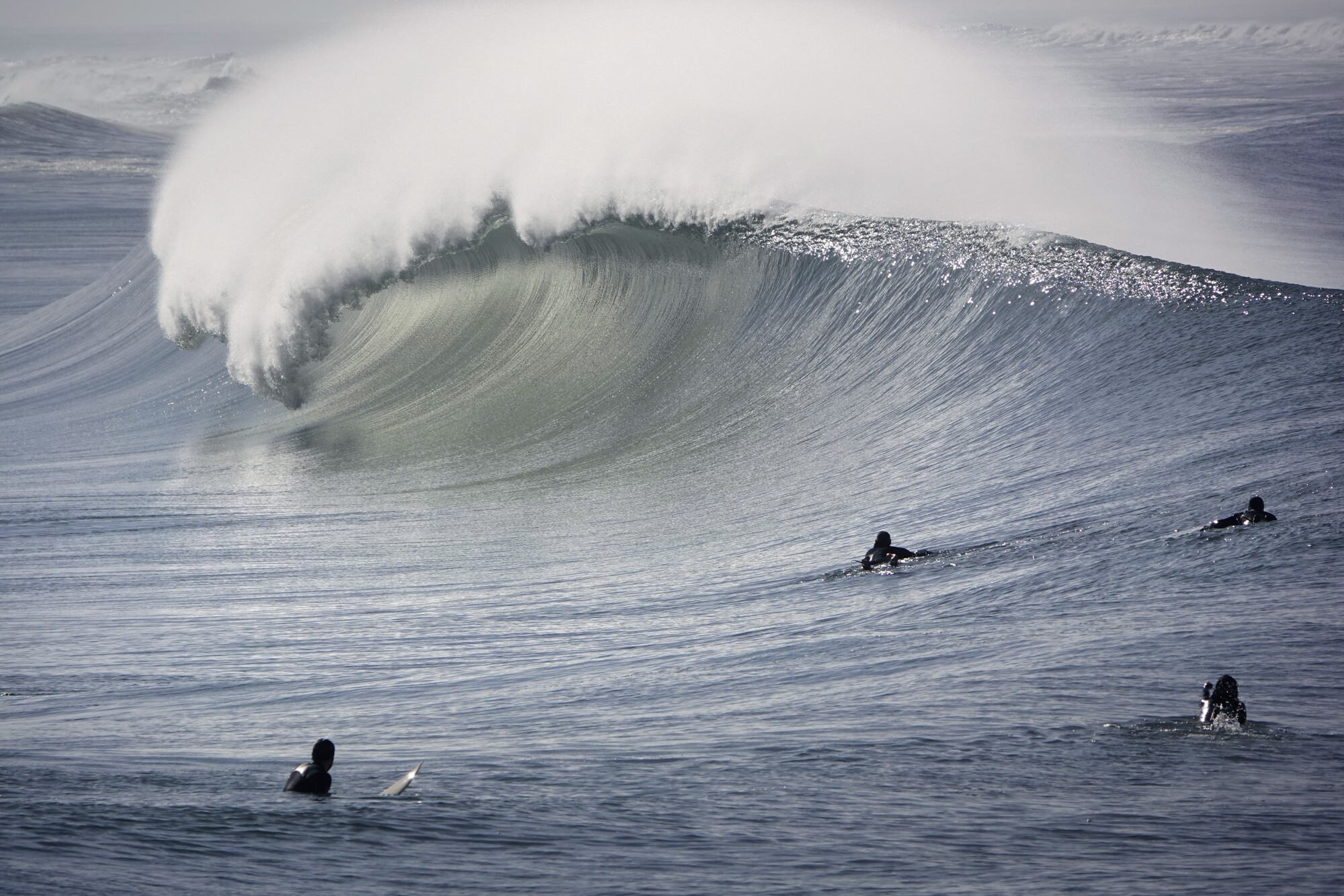 Surfers watch as a large wave breaks in Imperial Beach on Sunday, Jan. 3, 2021.