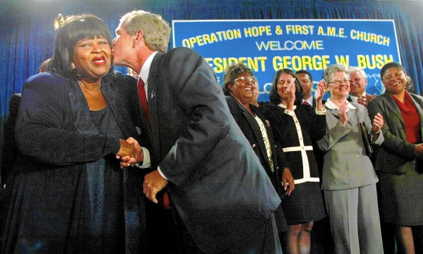 Marva Smith Battle-Bey receives a kiss from President George Bush in 2002. Smith Battle-Bey, an urban planning expert, was instrumental in bringing development to South L.A. over three decades.