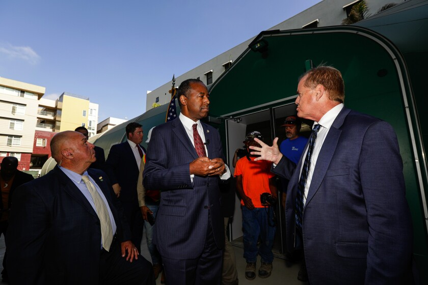 HUD Secretary Ben Carson, center, talks to Andy Bales, CEO of Union Rescue Mission, after touring the facility Wednesday.