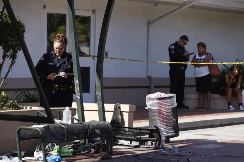 LAPD officer Rebecca Gordillo photographs the scene of an accident that involved a car into a bus stop at the intersection of Jefferson Blvd. and Vermont Ave. in Los Angeles. Two children and one adult were transported to local hospital according to officials on the scene.