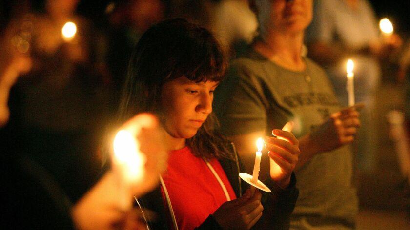 Valen Aznavourian, 12, of Glendale, watches the flame of her candle at a candlelight vigil in front of the church at the Lights for Liberty event at the La Cañada Congregational Church on Friday.