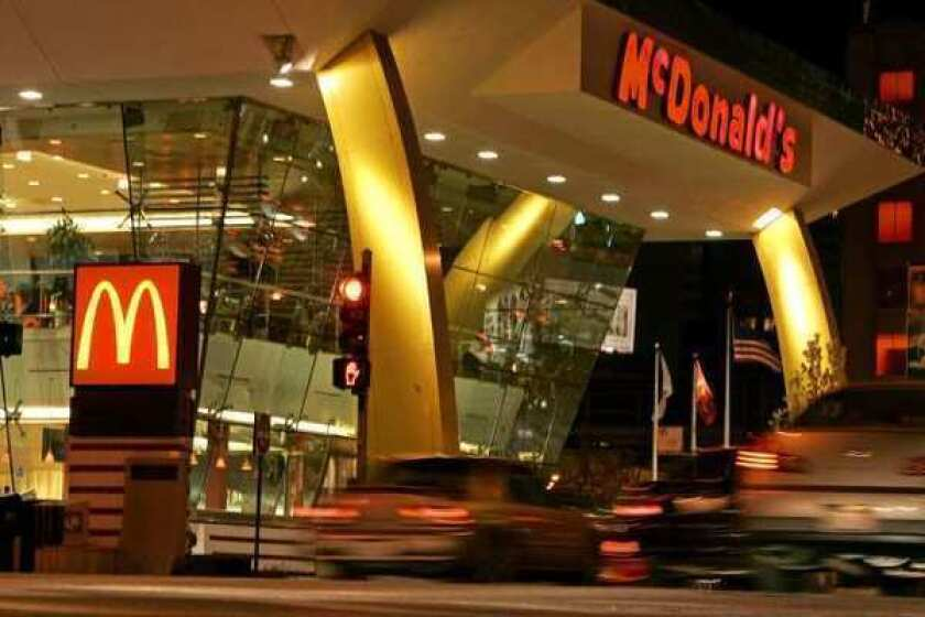 Cars drive past a McDonald's restaurant in Chicago. The chain will start posting calorie counts on all its menu boards and drive-through signs.