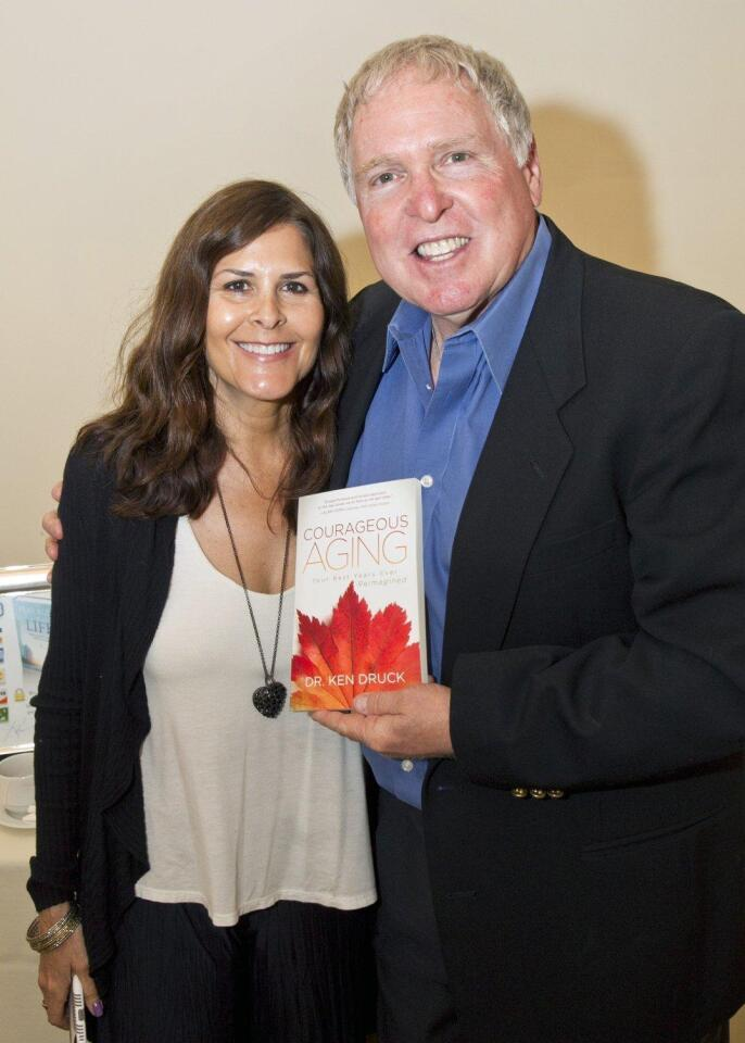 """Lisette Omoss and Dr. Ken Druck with his latest book """"Courageous Aging"""""""