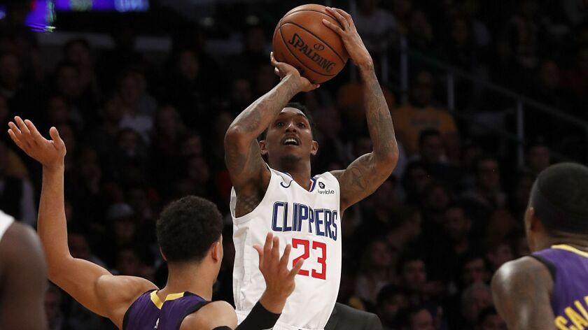 LOS ANGELES, CALIF. - DEC. 28, 2018. Clippers guard Lou Williams shoots over Lakers guard Josh Har