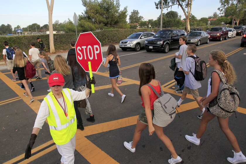 A crosswalk attendant stops traffic along Eastbluff Drive as students make their way to Corona del Mar High School in September.