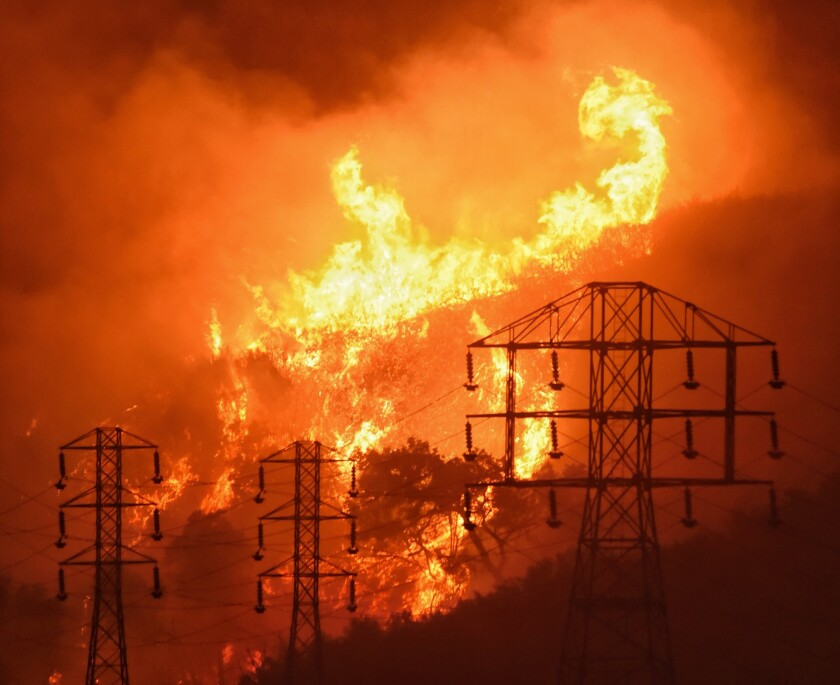 Flames burn near power lines in Sycamore Canyon in Montecito, Calif., on Dec. 16, 2017.