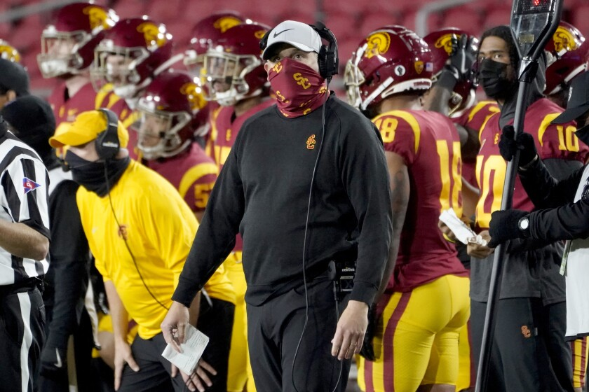 USC coach Clay Helton looks up from the sideline during a game against Washington State with USC players behind him.