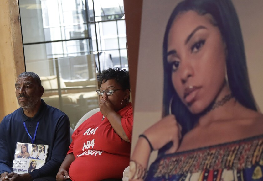 FILE - In this Aug. 17, 2018, file photo, a photo of victim Nia Wilson, right, is displayed at a news conference as her father Ansar El Muhammad, left, and her mother, Alicia Grayson, listen in San Francisco. An Alameda County jury found 29-year-old John Lee Cowell guilty of murdering Nia Wilson at the MacArthur BART station in Oakland as she was returning home from a family gathering with her two sisters. Jurors also found Cowell guilty of attempted murder in the stabbing of Wilson's sister, who survived severe injuries to her neck. Wilson's stabbing death in July 2018 horrified bystanders and added to BART's reputation as unsafe. (AP Photo/Jeff Chiu, File)