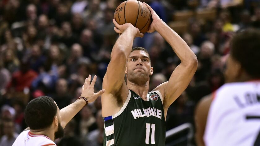 Bucks center Brook Lopez (11) lines up a three-point shot against the Raptors during a game earlier this season.