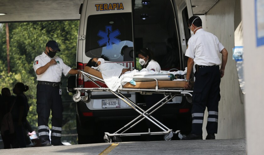 Medical workers carry a patient in respiratory distress from an ambulance May 20 at the Parque de Los Venados hospital in Mexico City.