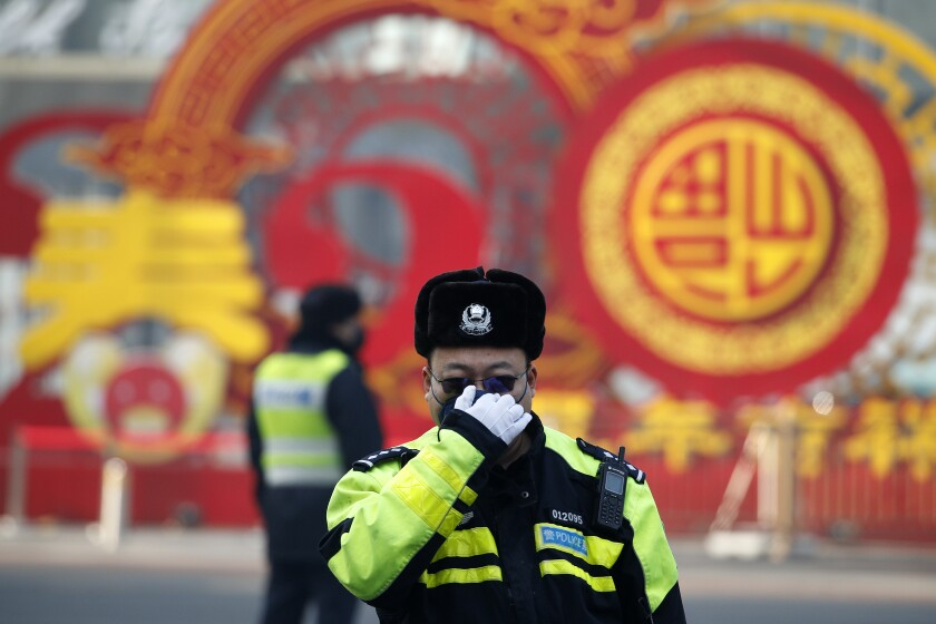 A policeman adjusts his mask in Beijing