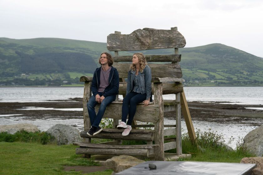 """Jedidiah Goodacre and Rose Reid sit on a giant wooden chair in a scene from the film """"Finding You."""""""