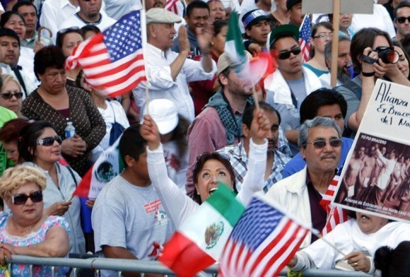 Backers of immigration reform take part in a May Day rally in downtown Los Angeles. A new poll finds that Latinos are growing less likely to report crimes to police for fear they will be questioned about their immigration status.