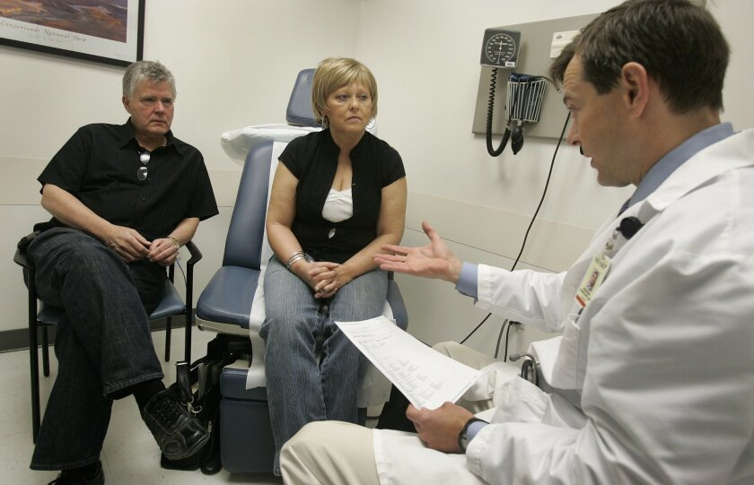 Jim Garlow, left, and his wife, Carol Garlow, center, talk with Andrew Hampshire, M.D., right, Carol's oncologist.