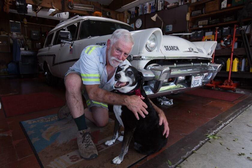 Self-styled highway rescue guy, Thomas Weller, in his El Cajon garage in 2015 with longtime sidekick, Shela.