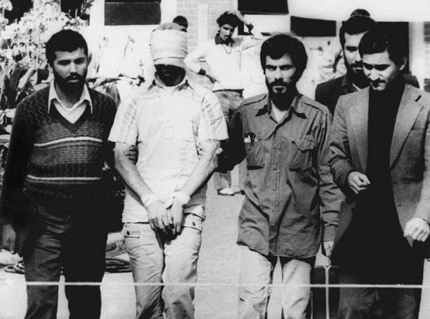 An American hostage, blindfolded and with his hands bound, was displayed to the crowd outside the U.S. Embassy in Tehran.