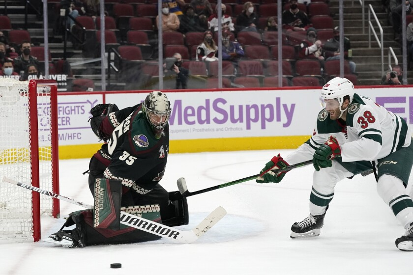 Arizona Coyotes goaltender Darcy Kuemper (35) makes a save on a shot by Minnesota Wild right wing Ryan Hartman (38) during the second period of an NHL hockey game Monday, April 19, 2021, in Glendale, Ariz. (AP Photo/Ross D. Franklin)