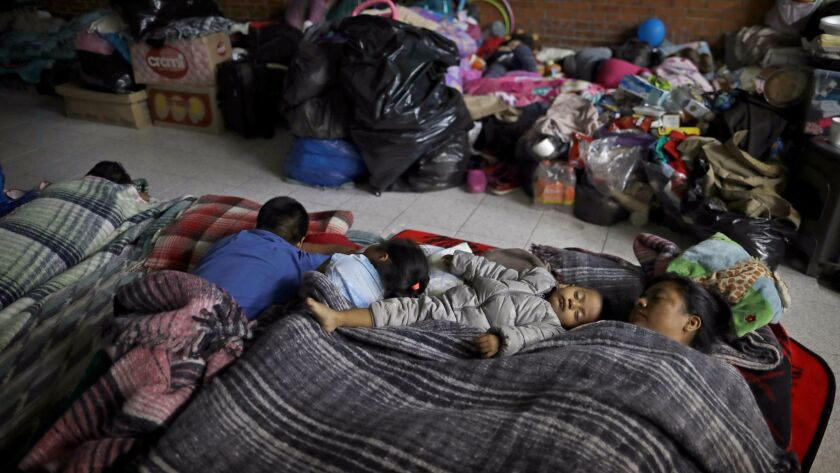 Florencia Cortes, 37, right, sleeps next to her son Jonatan at the Francisco Kino school, which was