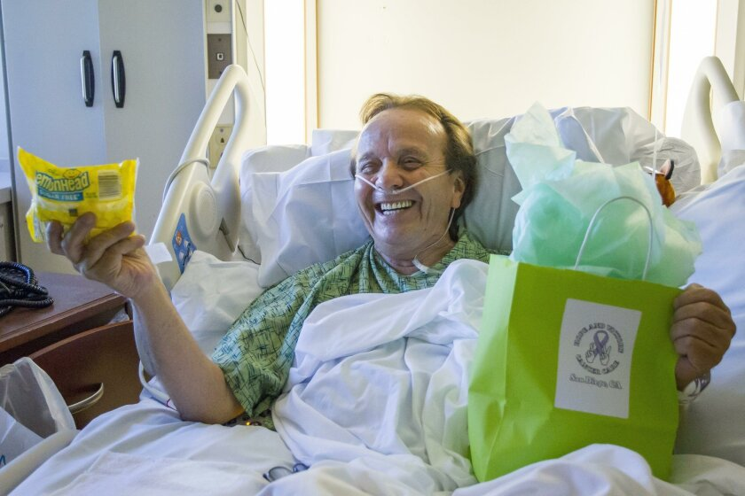 Francisco Enriquez, 66, diagnosed with small cell cancer in his lungs, laughs after finding Lemonheads in a gift bag, which will help him with taste and saliva production during chemo treatments.