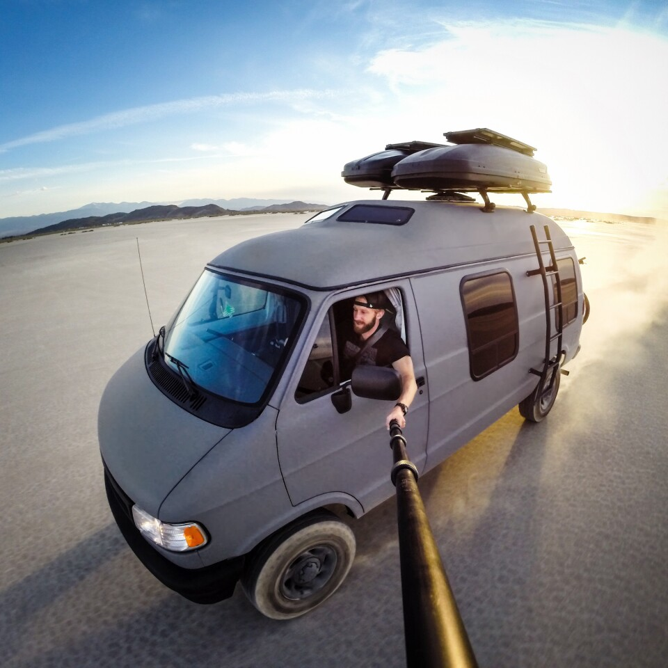 Using a long selfie stick, Travis Burke captures his van, Betty the Grey Wolf, in motion across desert sand. To see more, follow his adventures on Instagram- @TravisBurkePhotography.