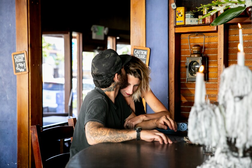 Customers Dan Lopez and Sara Minter share a quiet moment at Bleu Boheme while sitting at the bar as the restaurant reopens in the Kensington neighborhood on May 21, 2020 in San Diego, California. Restaurants began reopening for dine-in patrons on Thursday as the state and county began easing restrictions imposed during the coronavirus pandemic.