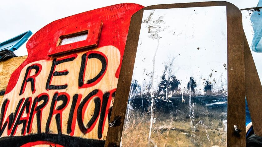 One of Cannupa Hanska Luger's mirror shields reflects police in riot gear at Standing Rock.