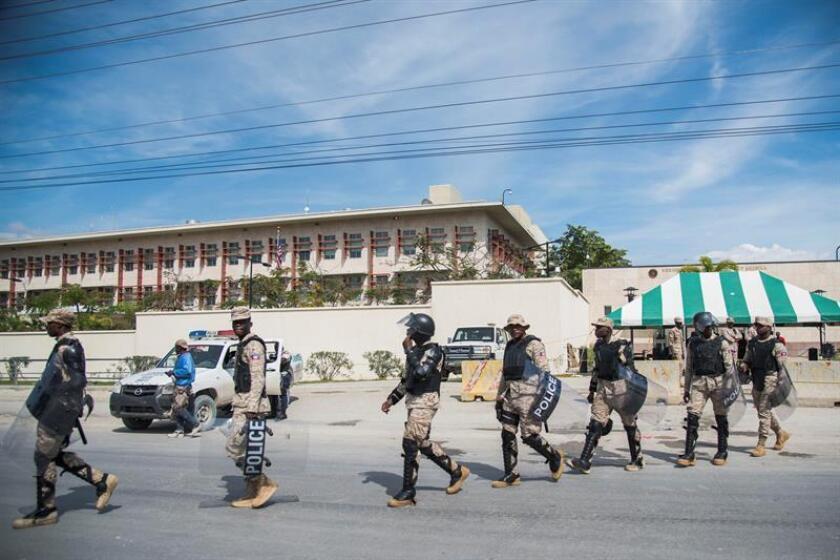 Miembros de la policía custodian la manifestación de centenares de haitianos frente a la embajada estadounidense en Puerto Príncipe (Haití). EFE/Archivo